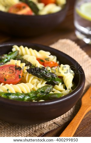 Baked green asparagus, cherry tomato and rotini pasta salad in rustic bowl, photographed on dark wood with natural light (Selective Focus, Focus on the asparagus head in the middle of the first bowl)