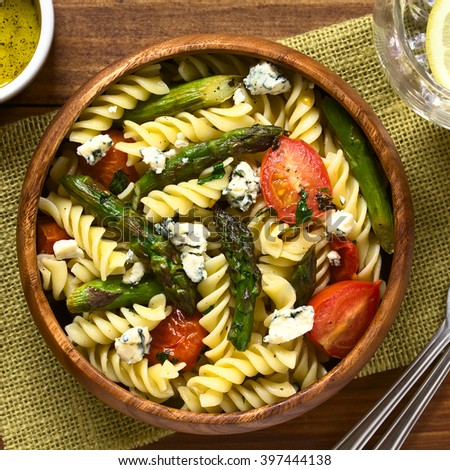 Baked green asparagus, cherry tomato, blue cheese and rotini pasta salad served in wooden bowl, photographed overhead on dark wood with natural light - stock photo