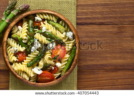 Baked green asparagus, cherry tomato, blue cheese and rotini pasta salad served in wooden bowl, photographed overhead on dark wood with natural light (Selective Focus, Focus on the top of the salad)