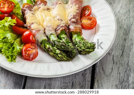 Baked green asparagus with prosciutto and cheese on a plate