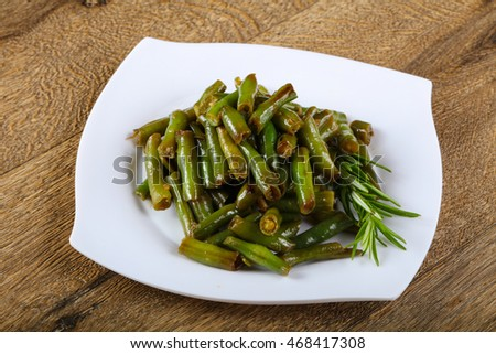 Baked green beans with rosemary on wood background