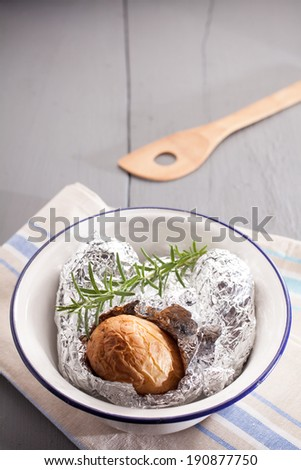 Baked jacket potato in aluminium foil hot off the barbecue lying on the crumpled foil wrapper in a basin with fresh rosemary, high angle view with copyspace - stock photo
