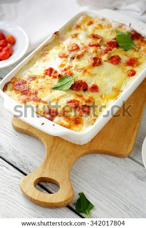baked lasagna in white dish with tomatoes - stock photo