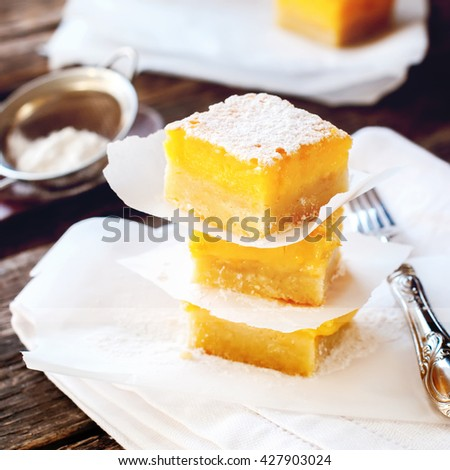 Baked Lemon Bars with Powdered Sugar Peaces in Tower Stack Wooden Table