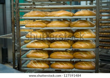 Baked long bread on rack trolley in bakery department in supermarket - stock photo