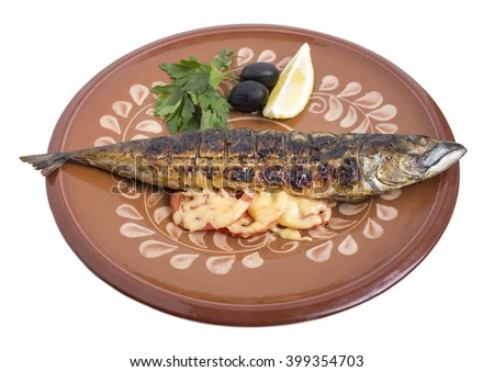 Baked mackerel on a clay plate with lemon and tomatoes. Isolated on a white background.