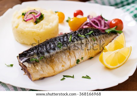 Baked mackerel with herbs and garnished with mashed potatoes and pickled vegetables - stock photo