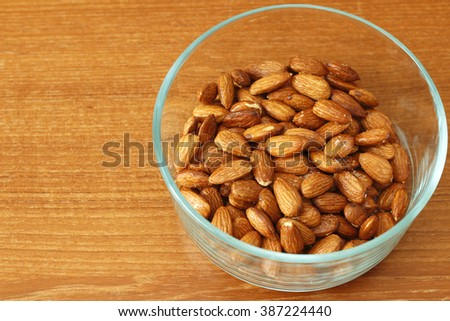 Baked maple syrup coated almonds with salt in a round glass bowl on a wooden table. A healthy and sweet snack of maple syrup coated dry almonds with salt in a bowl.