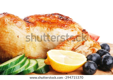 baked meat : fresh whole chicken with black olives and raw tomatoes on wooden board isolated over white background - stock photo