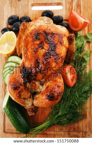 baked meat : homemade turkey with black olives and raw tomatoes on wooden board isolated over white background