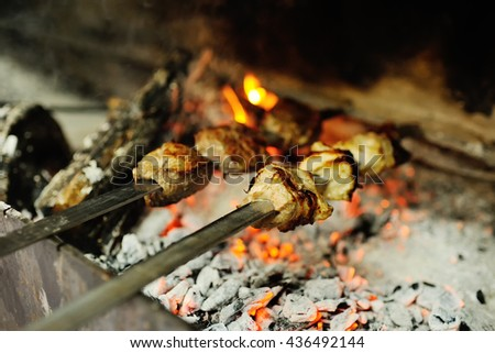 baked meat on the grill with vegetables. skewers of lamb