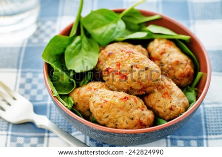 baked meatballs with pepper and spinach on a grey background. tinting. selective focus - stock photo