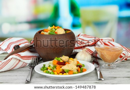 Baked mixed vegetable with chicken breast in pot, on bright background - stock photo