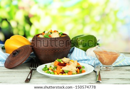 Baked mixed vegetable with chicken breast in pot, on bright background