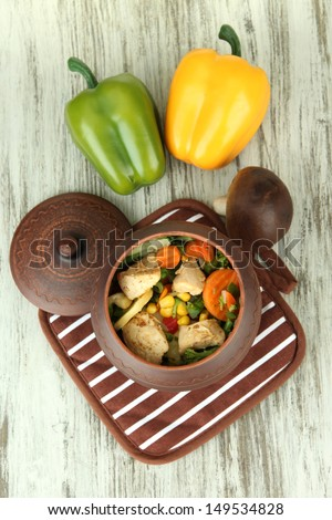 Baked mixed vegetable with chicken breast in pot on potholder, on wooden background - stock photo