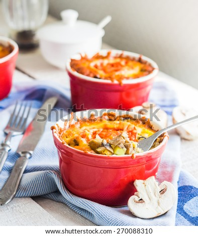 Baked mushroom julienne potatoes and tomato with cheese, lunch on a wooden background - stock photo