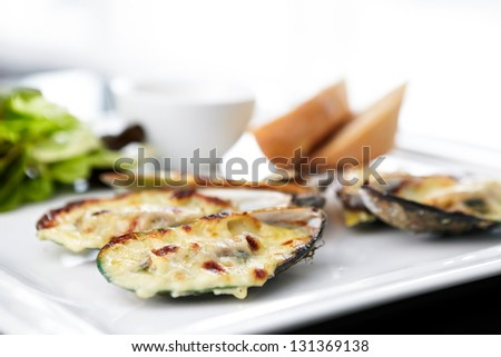Baked mussels au gratin with salad and sauce. - stock photo