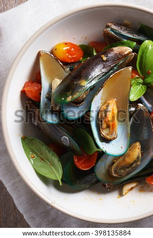 baked mussels with tomato and fresh sweet basil on table with bread