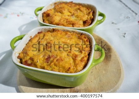 Baked or roasted egg pie or kind of quiche, french style snack baked in small roasting pan. Made from eggs, smoked ham, parsley, pork meat and bread. Traditional spring food in Czech Republic. - stock photo