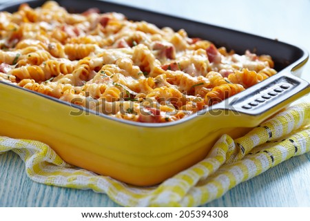 Baked pasta with ham and cheesy tomato sauce - stock photo