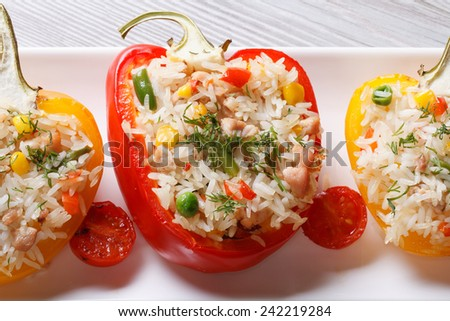 Baked peppers stuffed with rice, vegetables and meat close up on a plate. horizontal view from above  - stock photo