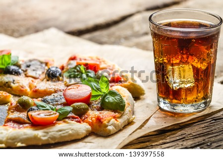 Baked pizza and served with cold drink - stock photo