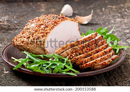 Baked pork decorated with arugula leaves - stock photo