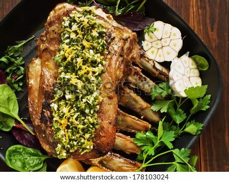 Baked pork ribs with gramalata garnish, veggies and lemon. Shallow dof.  - stock photo