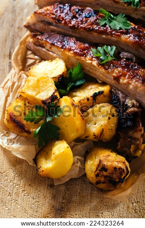 Baked potato and beef ribs splashed on wooden background,selective focus  - stock photo