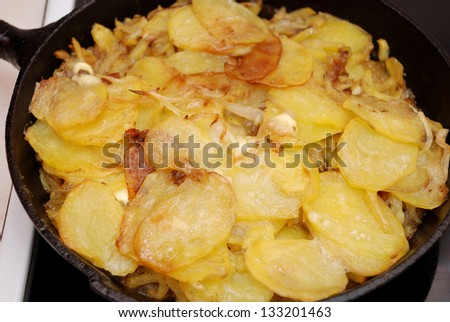 Baked potato and onion in the cast-iron frying pan