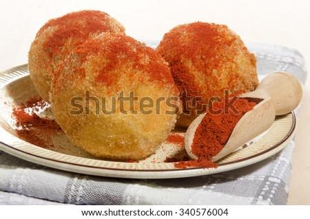 baked potato balls with paprika powder on a plate - stock photo
