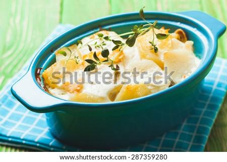 Baked potato casserole with cream sauce with thyme, gratin Dauphinois - stock photo
