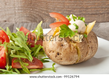 Baked potato filled with sour cream and arugula - stock photo