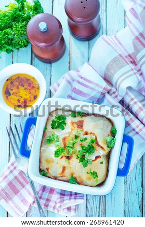 baked potato in bowl and on a table - stock photo