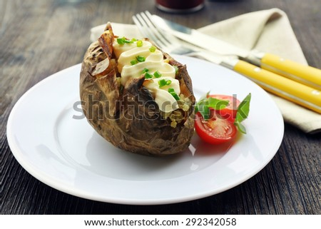 Baked potato mayonnaise and chives in white plate on wooden table, closeup - stock photo