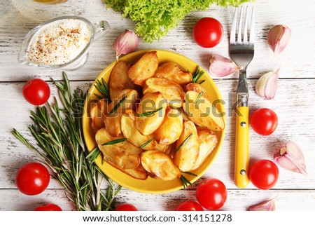 Baked potato wedges on wooden table, closeup - stock photo
