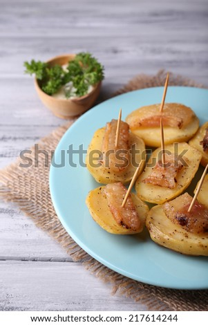 Baked potato with bacon on plate, on wooden background - stock photo