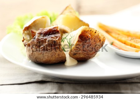 Baked potato with cheese and mushrooms on plate close up