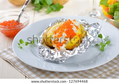 Baked potato with cream cheese and Russian trout caviar - stock photo