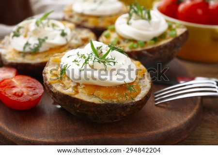 Baked potato with mayonnaise and herbs on wooden cutting board, closeup - stock photo