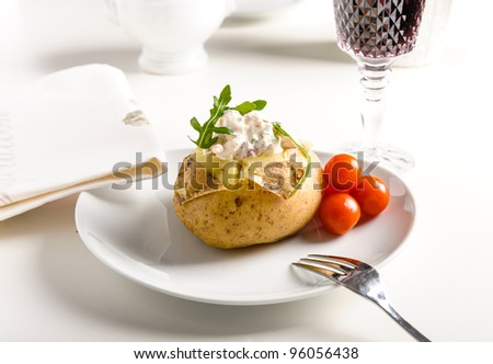 Baked potato with shrimps and some tomatoes - stock photo