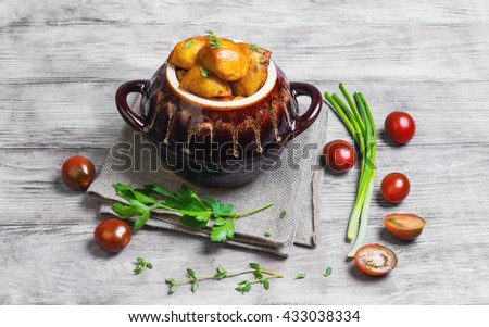 Baked potatoes in the oven in a special ceramic pot for roasting potatoes, chives, thyme, parsley, burlap cloth on a bright white background wooden - stock photo