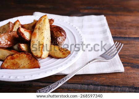 Baked potatoes on pate on wooden table - stock photo