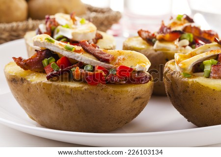 Baked potatoes stuffed with bacon and vegetables served with camembert - stock photo