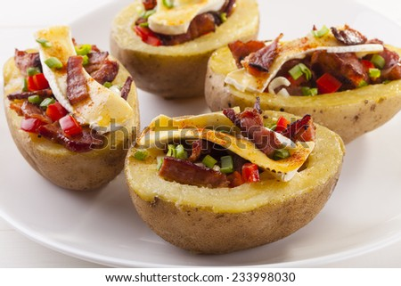 Baked potatoes stuffed with bacon and vegetables served with camembert