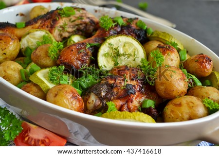 Baked potatoes with chicken and vegetables on a black background  - stock photo