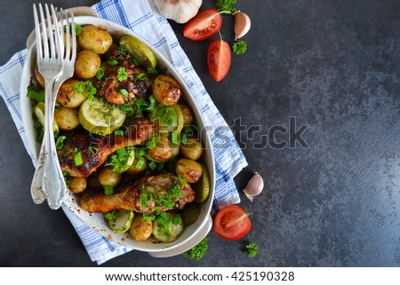 Baked potatoes with chicken and vegetables on a black background, with space for text - stock photo