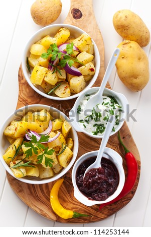 Baked potatoes with chutney and sour cream - top view - stock photo