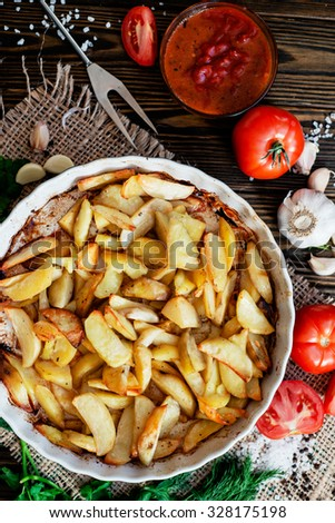 Baked potatoes with sauce , garlic , herbs and tomatoes on a wooden background - stock photo