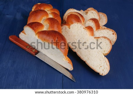 baked product : cut of challah over blue painted wooden board - stock photo